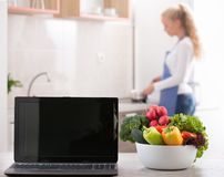 Vegetables and laptop in kitchen with woman cooking in backgroun. Vegetables in bowl and laptop on table with blurred woman in kitchen. Cooking and networking Stock Photography