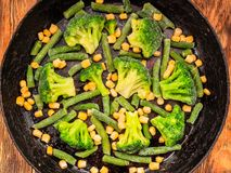 Vegetables broccoli corn green beans in a cast iron skillet. View from above stock images