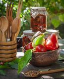 Vegetables in a brown clay dish and jars with canned eggplants Stock Images