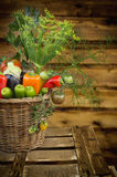 Vegetables bunch in basket on old wooden background Stock Images