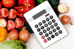 Vegetables with a calculator on white table Stock Image