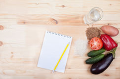 Vegetables and cereals and notebook on a wooden table. Healthy E Stock Photo