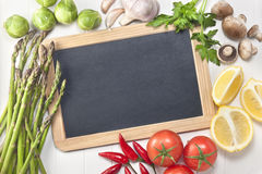 Vegetables Chalkboard Sign Background. Various fresh vegetables around the edge of a blank chalkboard sign on a white table background Stock Photography
