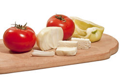 Vegetables with cheese. Fresh vegetables with cheese on the chopping board isolated on white background Stock Photography