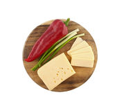 Vegetables and cheese on cutting board, isolated on white Royalty Free Stock Images