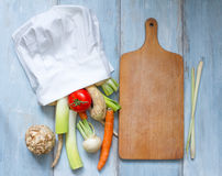 Vegetables in chef's hat and empty cutting board Stock Photos