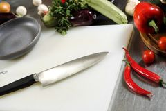 Vegetables and a chef`s knife are lying on a white cutting board at the bottom of the restaurant. royalty free stock image