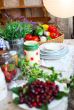Vegetables and cherries on a picnic table with plates and flowers Stock Photography