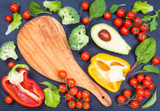 Vegetables and chopping board on rustic dark background. Different vegetables ingredients and chopping board top view on rustic background text space.Diet Royalty Free Stock Images