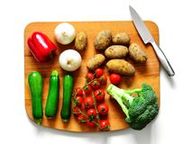 Vegetables on Chopping Board. Selection of freshly picked summer vegetables on chopping board with knife Stock Photography