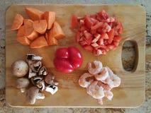 Vegetables on Chopping Board. Shrimps,  mushrooms, red bell pepper,  tomatoes on Chopping board Stock Image