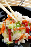 Vegetables an chopsticks. Chinese vegetables with chopsticks on a black plate Royalty Free Stock Images