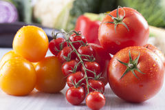 Vegetables. Close up photo of edible vegetables - cherry, yellow and red tomatoes with some vegetables in the background on a solid light blue wooden table stock photos