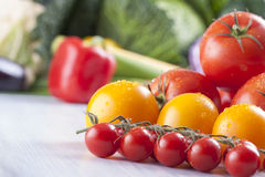 Vegetables. Close up photo of edible vegetables - cherry, yellow and red tomatoes with some vegetables in the background on a solid light blue wooden table Stock Images