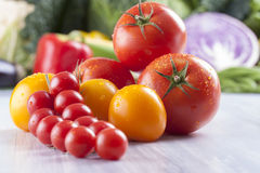 Vegetables. Close up photo of edible vegetables - cherry, yellow and red tomatoes with some vegetables in the background on a solid light blue wooden table Royalty Free Stock Image