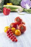 Vegetables. Close up photo of edible vegetables - cherry, yellow and red tomatoes with some vegetables in the background on a solid light blue wooden table Royalty Free Stock Photos