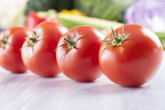 Vegetables. Close up photo of edible vegetables - a tomatoes with some vegetables in the background on a solid light blue wooden table stock photos