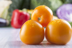Vegetables. Close up photo of edible vegetables - a yellow tomatoes with some vegetables in the background on a solid light blue wooden table Stock Photography