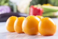 Vegetables. Close up photo of edible vegetables - a yellow tomatoes with some vegetables in the background on a solid light blue wooden table Royalty Free Stock Photos