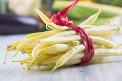 Vegetables. Close up photo of edible vegetables - a yellow wax bean with some vegetables in the background on a solid light blue wooden table stock photo