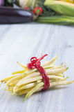 Vegetables. Close up photo of edible vegetables - a yellow wax bean with some vegetables in the background on a solid light blue wooden table royalty free stock photos