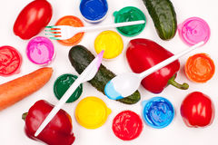 Vegetables and color paints. Motley paints, vegetables (tomatos, cucumbers, sweet peppers, carrot) and plastic fork, knife and spoon on the white background Stock Photo