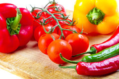 Vegetables for cooking on cuting board. Tomatoes, chilli, garlic and peppers for cooking on cutting board with knife Royalty Free Stock Image