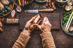 Vegetables cooking and eating. Women female hand peeling Jerusalem artichokes on dark rustic kitchen table background with various. Root vegetables ingredients Stock Photos