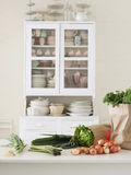 Vegetables On Counter With Utensils In Cupboard At Kitchen Stock Photos