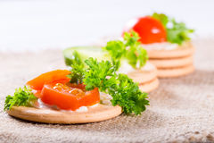 Vegetables on crackers: pieces of tomato and parsley Stock Images