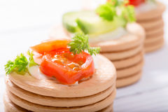 Vegetables on crackers: tomatoes, cheese and greens of parsley stock photo