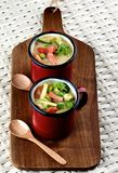 Vegetables Creamy Soup. Delicious Vegetables Creamy Soup with Broccoli, Carrots, Zucchini, Leek, Red Bell Pepper and Green Pea in Red Soup Cups with Wooden Spoon Stock Image