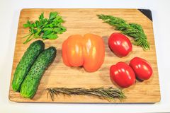 Vegetables cucumbers tomatoes sweet pepper parsley dill on a wooden board stock images
