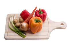 Vegetables on cutting board. Isolated on white background Royalty Free Stock Photos