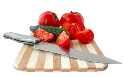 Vegetables on cutting board. Vegetables (tomatoes and cucumber) with knife on bamboo cutting board Royalty Free Stock Photography