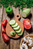Vegetables on cutting board on dark wooden background stock images