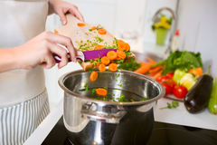Vegetables on the cutting board are falling in the pot Stock Photography