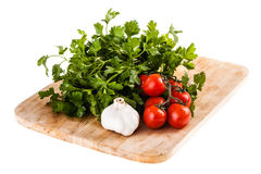 Vegetables on a cutting board over white. Some cherry tomatoes, parsley and garlic on a cutting board isolated over a white background Royalty Free Stock Images