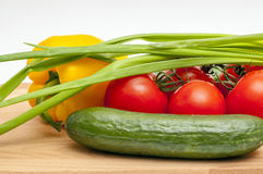 Vegetables on a cutting board. Vegetable composition: cucumbers, tomatoes, onion and pepper on a cutting board Stock Image