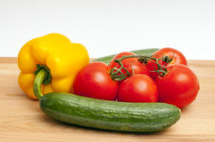 Vegetables on a cutting board. Vegetable composition: cucumbers, tomatoes and pepper on a cutting board Stock Image