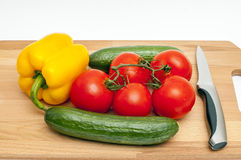 Vegetables on a cutting board. Vegetable composition: cucumbers, tomatoes and pepper on a cutting board with a knife Royalty Free Stock Images