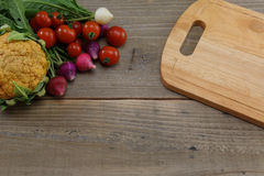 Vegetables and cutting board on a wooden background Royalty Free Stock Images