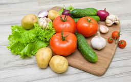 Vegetables on a cutting board on a wooden table Stock Images