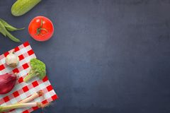 Vegetables on dark kichen table. Zucchini, tomato, chocolate, broccoli, onion, onion, broccoli and table cloth on table. Free space for text Royalty Free Stock Image