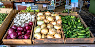 Vegetables on display at a produce stand. Display of onions, garlic and cucumbers at a roadside produce stand royalty free stock photography