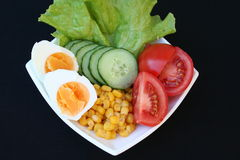 Vegetables and egg for salad. Egg,tomato,maize,cucumber and lettuce on plate to be prepared as a healthy salad Stock Photo