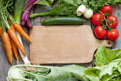 Vegetables and empty cutting board background Stock Images