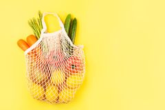 Vegetables in fabric shopping bag on yellow background stock image