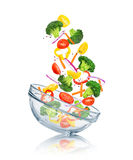 Vegetables falling into a glass bowl Stock Images