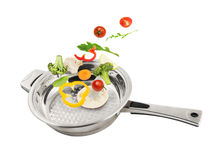 Vegetables falling in the pan Royalty Free Stock Image